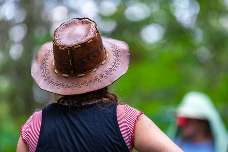 Selective focus close up of woman wearing cowboy leather hat viewed from the back, with blurred background of nature and people