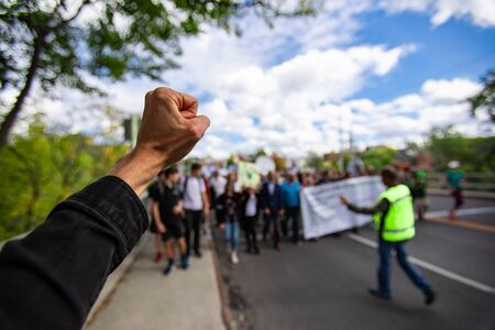 First person perspective and Selective focus on man fist raised during an ecological protest. Crowd of people walking with security in the background