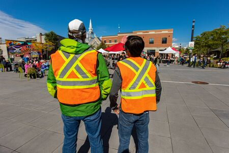 Two men from the back with high emergency clothing at public space protecting and looking out at climate change protest.