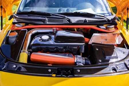 Petite voiture jaune sous le capot montrant le réglage et la modification du moteur haute performance, pièces propres en rouge, argent, chrome et fibre de carbone