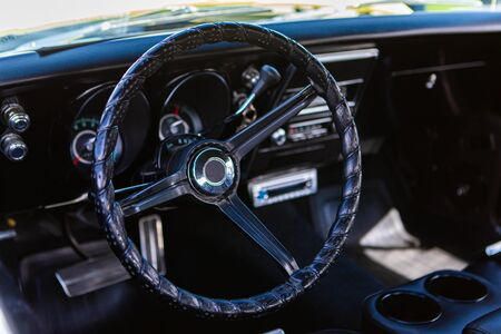 close up and selective focus on antique car black leather steering wheel, simple old style interior, and Dashboard Counters background Stockfoto