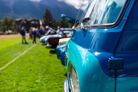 Old Vintage Classic American turquoise blue van car front, side view close up on the grass during an outdoor show, people and cars in the background Stock Photo