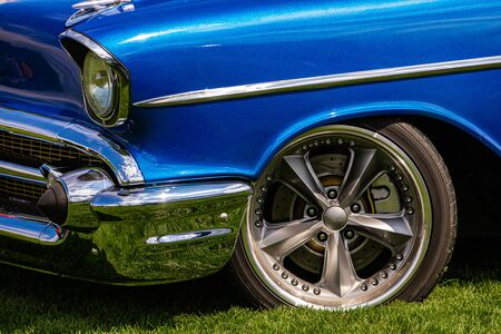 Old antique classic American blue car front on the grass with a chrome bumper and body parts, front wheel side close up view, sports star wheel rim