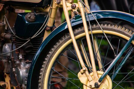 vintage classic old motorcycle with bright cream white and Duck Blue color, close up view of the front wheel and engine parts Zdjęcie Seryjne