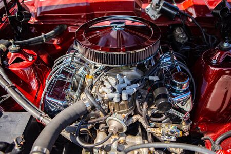 red classic muscle car under the hood, v8 engine with big chromed round air intake filter, tubes, wires, pipes, mechanical and electrical other parts