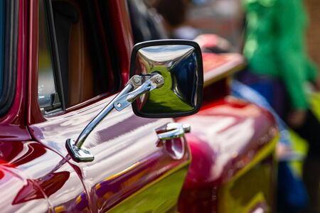 classic antique American red pickup car side chrome mirror close up view, people in the background during outdoor old cars show Imagens
