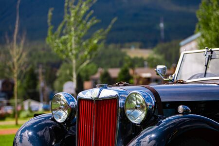 Classic antique black convertible, cabriolet car front details with red Grille and chrome body parts, big Headlamp lights, outdoor background
