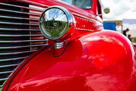 Old vintage American bright red pickup car front side close up view, with chrome glass headlights light lamp parts and grille during an outdoor show Foto de archivo
