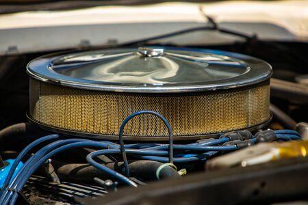 Primo piano e messa a fuoco selettiva su un grande filtro di aspirazione dell'aria tondo cromato su un classico motore di muscle car, con fili blu, cavi ad alta tensione Archivio Fotografico