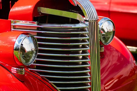 Old vintage American red pickup car front half side view close up, chrome headlights light lamp and grille, with open hood during an outdoor show