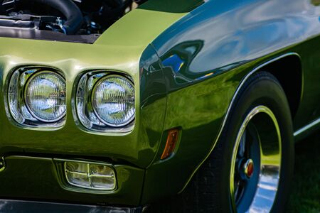 old vintage American muscle green car half front right side, with open hood and close up on headlights light lamps, with large rim wheel Foto de archivo