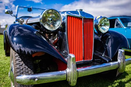 Classic antique black convertible, cabriolet car front details with red Grille and chrome body parts, big Headlamp lights, low angle outdoor view Zdjęcie Seryjne