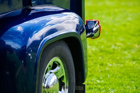 close up on bright blue vintage classic pickup car rear wheel with silver chrome rim and Backlight, blurred grass background Zdjęcie Seryjne
