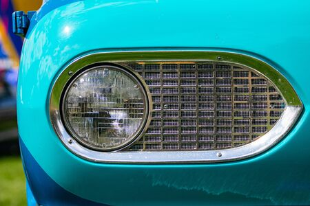 Turquoise blue old classic antique American car half front, left side, close up on glass headlight with metallic chrome frame