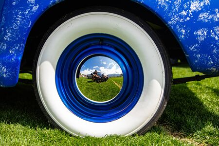 vintage classic American bright blue car wheels on the grass, Close up on the Steel Wheel Chrome center With reflection, and Whitewall tire Zdjęcie Seryjne