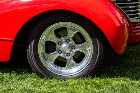 Old classic American bright red car wheel on the grass, chrome star rim with five lugs, Car tuning with Low sport suspension Zdjęcie Seryjne