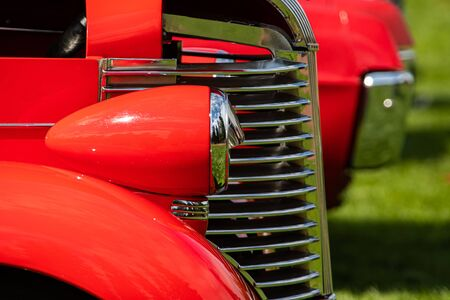 Old vintage American red pickup car front half side view close up, chrome headlights light lamp parts and grille with open hood during an outdoor show