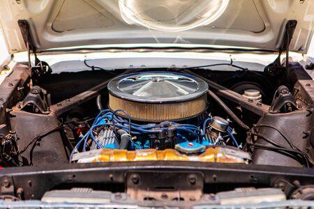 vecchia auto classica a cofano aperto con motore v8 e grande filtro di aspirazione dell'aria tondo cromato con fili di candele blu, cavi dell'alta tensione.