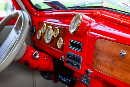 bright red classic antique car Dashboard with wooden and golden parts, white leather steering wheel, simple old cars interior style close up