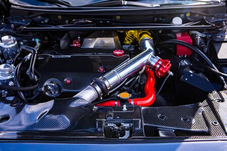 Car under hood showing high performance transverse engine with tuning and modification, red, yellow, silver, chrome and carbon fiber clean parts Zdjęcie Seryjne