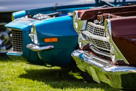 Old antique Classic American red and blue fast cars front, side view on the grass during an outdoor show, with chrome body parts and open hood 스톡 콘텐츠