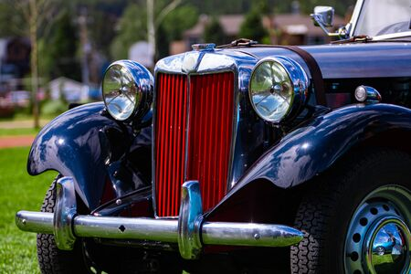 Old Classic antique black car front details with red Grille and chrome body parts and big Headlamp lights and small lamps, outdoor background Zdjęcie Seryjne
