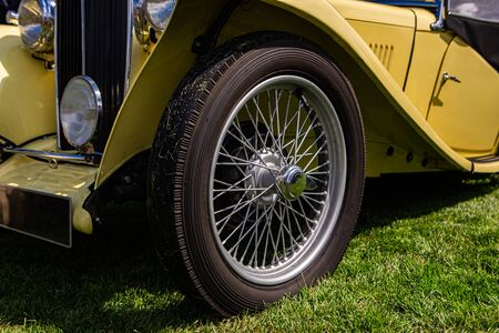 Classic antique car in cream white color on the outdoor grass, the right front wheel view, Vintage Wire Wheel rim, and thin tire