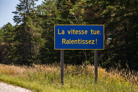 Blue Information Road Sign with french yellow writing, Speed kills. Slow down !, on rural country roadside, forest trees background, Ontario, Canada
