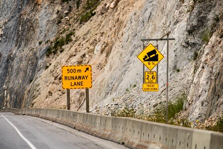 Steep hill 6 percent ahead for 2.6 km, truck gear down. 500 m runaway lane. Warning road signs and cement barriers on the right roadside Reklamní fotografie