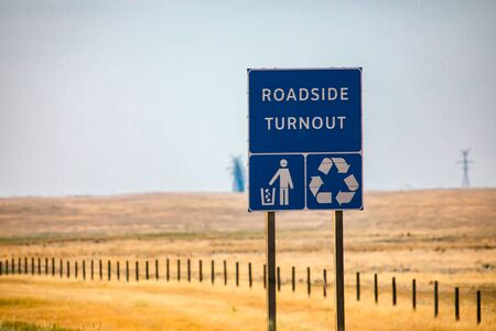 Information Road blue Sign, Roadside turnout with Tidy man and Recycling symbols on Canadian rural country roadside against yellow prairies and plains
