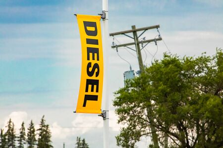 DIESEL fuel symbol, gasoline station, selective focus on yellow exhibition sign on a light pole, trees and wooden Electric Pylon in the background Reklamní fotografie