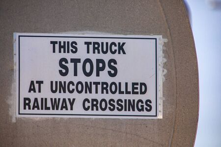 selective focus and close up view on Warning white a poster sign says This truck STOPS at uncontrolled railway crossing, on metal tank truck back