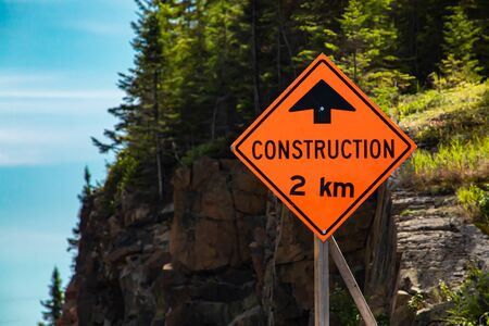 Construction work two kilometer ahead, Temporary condition road signs, close up selective focus on warning orange symbol with Rocky slope background