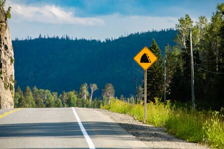 Watch for fallen rock and be prepared to avoid a collision sign. Warning Road Signs on the roadside with pine trees forest background