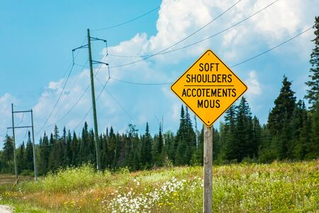 SOFT SHOULDERS, Accotements mous, Bilingual road warning signs on roadside, selective focus view with forest trees background Reklamní fotografie