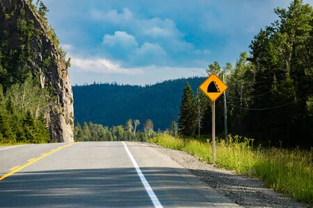 watch for fallen rock and be prepared to avoid a collision sign. with a Rocky slope on the left roadside, Warning Road Signs. Reklamní fotografie
