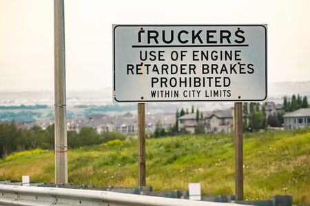 Information Road white Sign on the Canadian highway roadside, Truckers, use of engine retarder brakes prohibited, within city limits