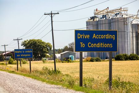 French, English Information road Signs, Drive According To Conditions. Canadian rural country roadside, grain silos in the background, Ontario Canada