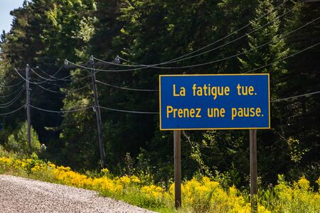 Blue Information Road Sign with french yellow writing, tiredness kills. take a break., on rural country roadside, trees background, Ontario, Canada