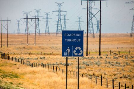 Information Road blue Sign, Roadside turnout with Tidy man and Recycling symbols against yellow prairies and plains and electrical lattices background