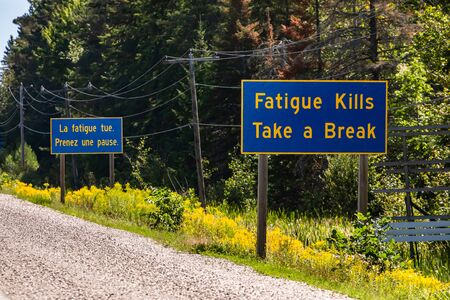 French and English Information road blue signs, tiredness kills. take a break. Canadian rural country roadside, Ontario, Canada Reklamní fotografie