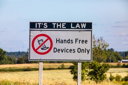 Its the law, hands free device only with no mobile symbol., Information Road white Sign on Canadian rural country roadside against prairies, plains