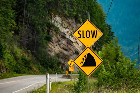 slow, Watch for fallen rock and be prepared to avoid a collision, Warning yellow roads signs in selective focus view with rocky slope background