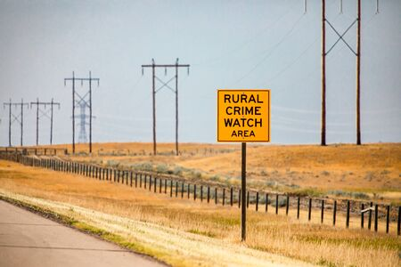 Information Road yellow Sign, Rural crime watch area, on country roadside against yellow prairies and plains and electrical lattices in the background