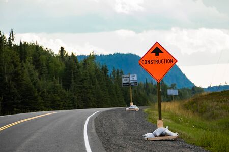 Temporary condition road signs, Construction work. on Canadian rural country roadside with pine trees forests background, warning orange symbol