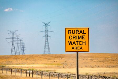 Information Road yellow Sign, Rural crime watch area, Canadian country roadside against yellow prairies and electrical lattices in the background Reklamní fotografie