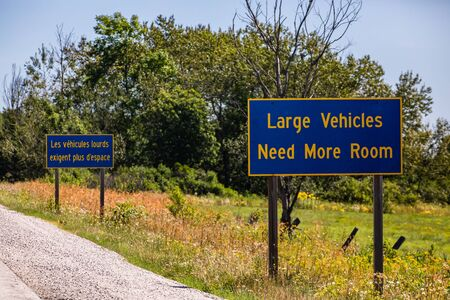 French, English Information Road Signs, large vehicles need more space. on Canadian rural country roadside, forest trees background, Ontario, Canada