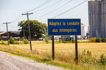 French Information Road Sign, Adapt the driving to the weather., on the rural country roadside, with grain silos in the background, Ontario, Canada