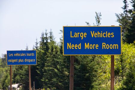 French and English two Information road Signs, large vehicles need more space. on the Canadian rural country roadside, Ontario, Canada
