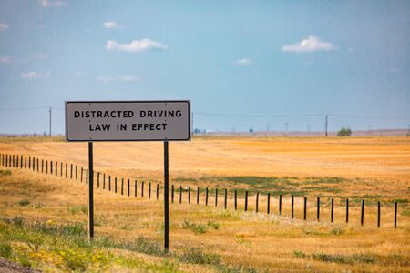 Information Road white Sign, Distracted driving law in effect., on Canadian rural country roadside, against yellow prairies and plains